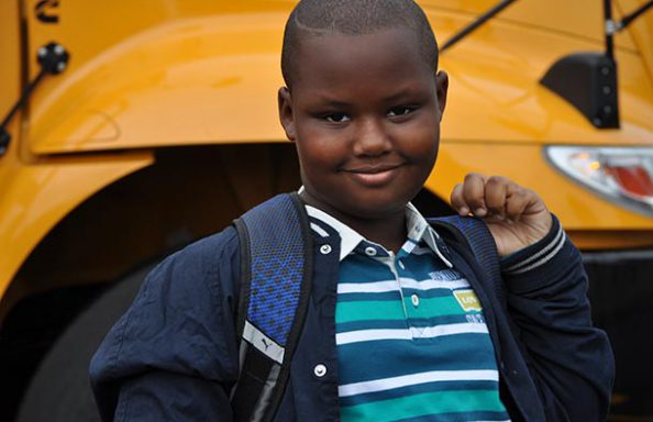 Stonehedge Boy Near School Bus on First Day
