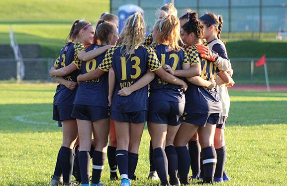 Athletics Girls Varsity Soccer Team in Huddle